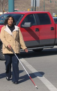 Personal Adjustment to Blindness Training client crossing street using a white cane
