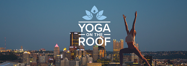 Image of a person doing yoga this the Pittsburgh Skyline in the background
