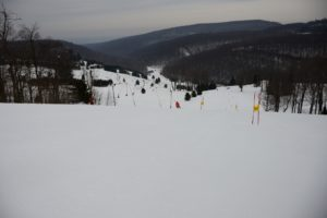 looking down a ski slope with racing gates and snow and tree covered covered mountains in the background