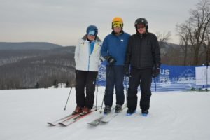 3 smiling men standing together wearing helmets and goggles 2 wearing their skies with trees and snow behind them.