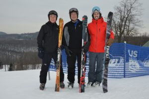 3 smiling men standing together wearing helmets and goggles holding their skies with trees and snow behind them.