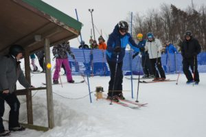 Many skiers and snowboarders standing around with 1 skier in blue jacket waiting to start racing