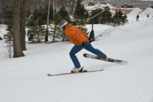 Skier in black helmet, orange jacket and blue pants with 1 ski raised to the side with trees and snow around.