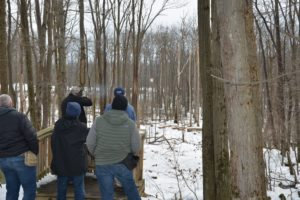 group of 5 shooters 2 standing on a platform 1 holding a rifle shooting a flying disc all facing woods with snow around