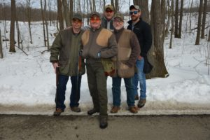 5 smiling men from Vista Metals standing close together holding their rifles with trees and snow behind them