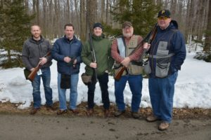 5 smiling men from PJ Dick standing close together some holding their rifles with trees and snow behind them