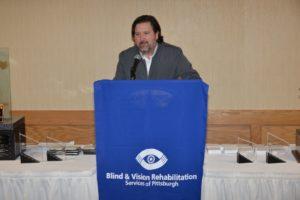 man standing at a podium speaking