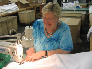 Woman in Blue shirt sewing white fabric