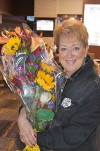 woman in a denim jacket smiling holding a large bouquet of flowers.