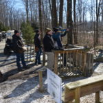 Group standing outside in and near a shooting stand one is shooting a rifle