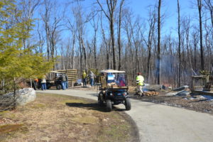 image of carts on a path in a stand of trees with a fire on the right, there a several people in the image as well