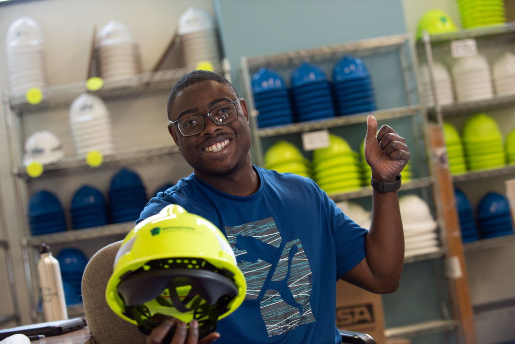 Image of a man in a blue shirt holding a yellow construction helmet out in front of him with his left hand in the air pointing his thumb up, there are shelves of helmets behind him